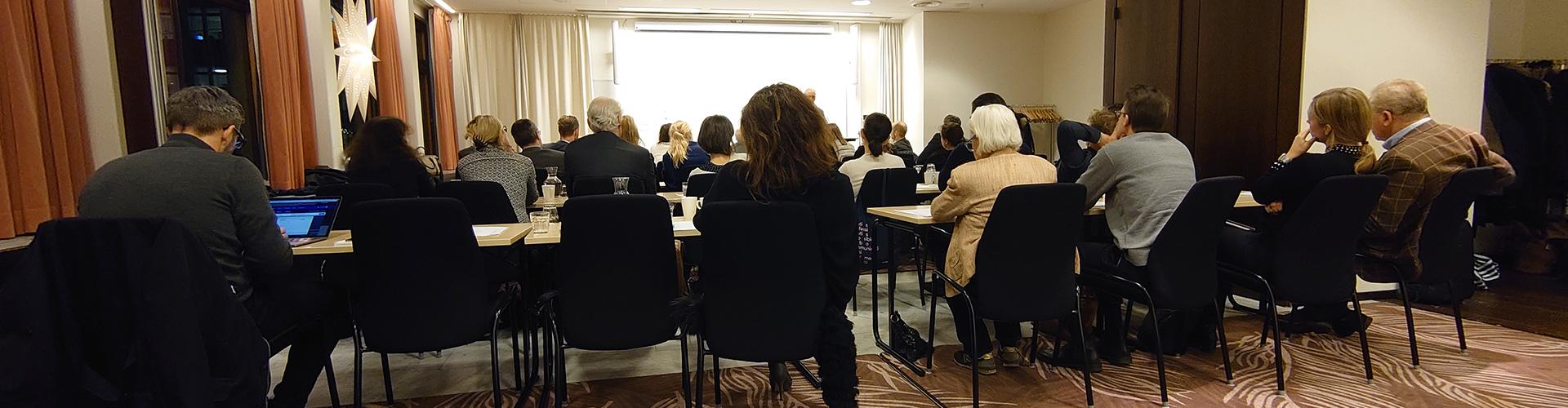människor som sitter vid bord och lyssnar på föreläsning