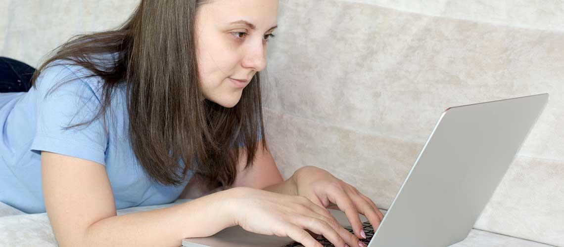kvinna liggande på magen framför dator i en soffa
