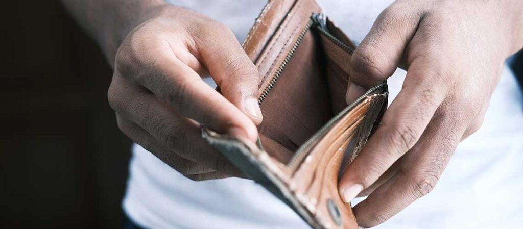 person som håller en plånbok